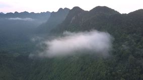 Aerial motion to fluffy cloud hanging on high mountain chain stock video footage