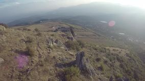 Aerial of mountain bikers ride downhill in mountains Besh-Kosh. Crimea. stock video footage
