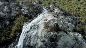Aerial: mountain waterfall flows over the rocks. Above the huge mountain glacier.