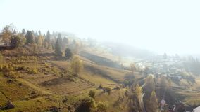 Aerial mountains valley fog drone village. Aerial shot in the valley of the mountains village fog sun winter spring stock footage