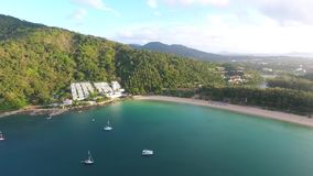 Aerial: Nai Harn beach in sunrise time look around. HD birds eye view. Blue water with rocks, jungle on background. Aerial: Nai Harn beach in sunrise time look stock video