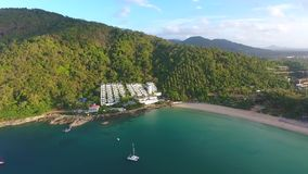 Aerial: Nai Harn beach in sunrise time look around. HD birds eye view. Blue water with rocks, jungle on background. Aerial: Nai Harn beach in sunrise time look stock video footage