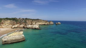 Aerial from natural rocks at Praia Tres Irmaos Alvor Portugal stock footage