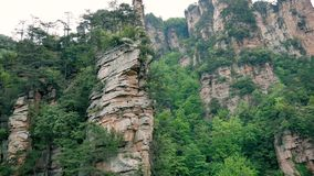 Aerial Near The Rock Pillars In The Zhangjiajie Mountains With Tropical Forest. Aerial near vertical high cliff pillars and columns in the mountains of stock video