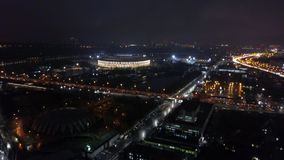 Night Moscow with Luzhniki Stadium, aerial view. Aerial night scene of Moscow, Russia. City lights in the darkness, traffic in the streets and illuminated stock video