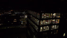 AERIAL: Night shot of an office building in business district stock video