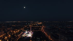 Aerial night view of lighted ferris wheel in amusement park against sky with moon, Valencia, Spain stock video footage
