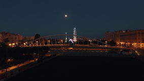 Aerial night view of lighted ferris wheel and bridge against sky with moon , Valencia, Spain stock video footage