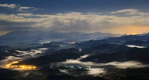 Aerial night view of mountain with light and fog stock photo