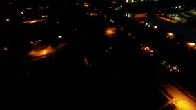 Aerial night view of residential suburban neighborhood with street lights and rooftops