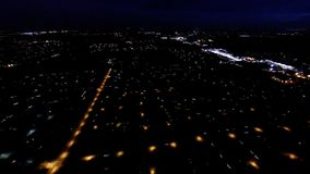 Aerial night view of residential suburban neighborhood with street lights and rooftops. Night view of house lights, streets and buildings from in air flight stock video footage