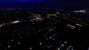 Aerial night view of residential suburban neighborhood with street lights and rooftops. Night view of house lights, streets and buildings from in air flight stock video