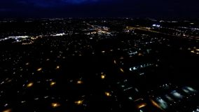 Aerial night view of residential suburban neighborhood with street lights and rooftops. Night view of house lights, streets and buildings from in air flight stock footage