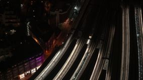 Aerial night view of train station, trains slowly moving from illuminated platforms, cars driving on streets.  stock video footage