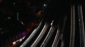 Aerial night view on train station, trains slowly moving from platforms.  stock footage