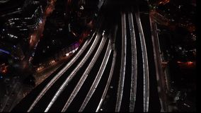 Aerial night view of train station, trains slowly moving from platforms, cars driving on streets, pedestrians walking on platforms.  stock footage