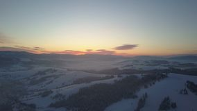 Aerial nordic winter landscape flight over snow mountain forest on sunrise. Winter drone flight over mountains through a stock video