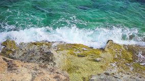 Aerial view of turquoise sea at sunny day. Top view of waves splashing against rocks in slow motion. Aerial ocean view of turquoise sea at sunny day. Top view of stock footage