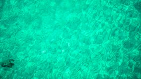 Aerial ocean view of turquoise sea at sunny day. Top view of waves on surface of clear blue seawater. Aerial ocean view of turquoise sea at sunny day. Top view stock footage