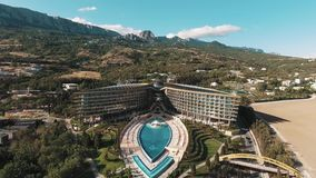 Aerial over elite hotel with pool and fountains under mountains on sunny day stock video footage