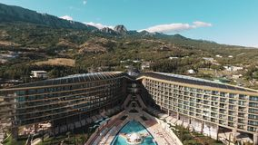 Aerial over expensive hotel with pool and fountains under mountains on sunny day stock footage