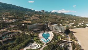 Aerial over modern hotel with pool and fountains under mountains on sunny day stock video