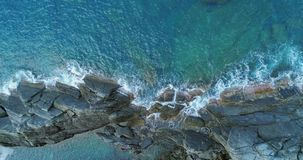 Aerial overhead view of ocean mediterranean sea waves reaching and crashing on rocky shore beach coast. Sunny weather stock video footage