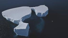 Aerial overview of iceberg among Antarctica ocean. Drone Flight Over Huge Ice Mountain. Sunlit Cold Ocean Water. Winter Antarctic Landscape. Wilderness. Virgin stock video footage