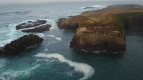 Aerial of Pacific Ocean and Rocky Seashore in California stock footage