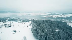 Aerial pan shot of a snow covered alpine skiing slopes in winter. Ski resort in southern Poland, the Tatra mountains. Aerial view of a snowy ski resort stock video