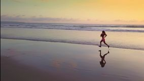 Aerial panning with drone on attractive and sexy Asian sport runner woman in running workout practice at sunset beach backlit. As silhouette in fitness and stock video