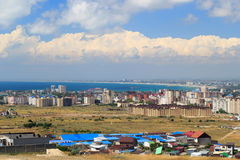 Aerial panorama of Anapa resort city, Russia. Summer day under blue cloudy sky. View from mountain. New buildings, construction cranes and Black Sea water stock image