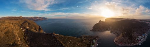 Aerial panorama of Balaklava, Crimea mountain cliffs in enter to bay at sunset. Beautiful nature landscape with sea and coastline. View from above royalty free stock photo