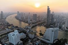 Aerial panorama of Bangkok at dusk with busy traffic on Taksin Bridge, boats & ferries on Chao Phraya River and skyscrapers stock image