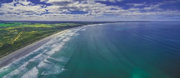 Aerial panorama of beautiful ocean coastline, white sandy beach, and farm lands in Australia. Stock Images