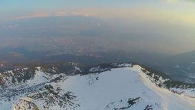 Aerial panorama of big city at mountain bottom in Austrian Alps, high snowy peak stock footage