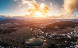 Aerial panorama of Crimean nature landscape with sunset, hills, lakes for fishing and small village with road, drone shot stock image