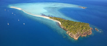 Aerial panorama of exotic remote island. Surrounded by turquoise water, reef and vacation yachts Royalty Free Stock Images