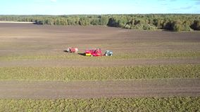 Aerial view truck pulls away from potato combine on field