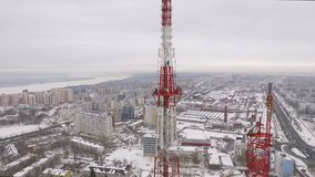 Aerial panorama of large city and Telecommunications tower, radio and tv broadcasting. Drone is flying in winter stock video