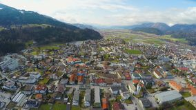 Aerial panorama of modern town in green Alpine valley, beautiful mountain nature. Stock footage stock video