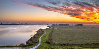 Aerial panorama of Netherlands Polder landscape. With winding cycling track along river under beautiful sunset Stock Images