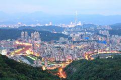 Aerial panorama of overpopulated suburban communities in Taipei at dusk. With Taipei 101 Tower in downtown, bridges over Xindian River & distant mountain Royalty Free Stock Photos