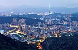 Aerial panorama of overpopulated suburban communities in Taipei at dusk with view of Taipei 101 Tower in downtown & bridges. Over Xindian River Royalty Free Stock Photos