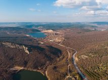 Aerial panorama of road in hill terrain with lakes, view from above.  royalty free stock photography