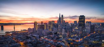 Panorama of the San Francisco skyline with brilliant sunrise. Aerial panorama of the San Francisco skyline silhouetted against colorful brilliant sunrise royalty free stock images
