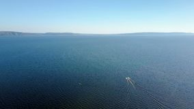 Aerial panorama of a sea, with two moving yachts in a frame, drone is flying from open sea to coast. With picturesque mountains in sunny weather stock video