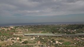 Aerial panorama shot of a highway and the sea in the background stock footage