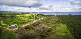 Aerial panorama of stormy clouds above wind turbines and pastures on ocean shore. Aerial panorama of stormy clouds above wind turbines and pastures on ocean Royalty Free Stock Images