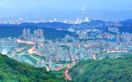 Aerial panorama of suburban residential communities in Taipei, with view of Taipei 101 Tower among skyscrapers. Romantic Taipei in blue twilight Royalty Free Stock Photography